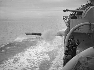 HMS Shropshire - Members of the ship's company watching a torpedo leaving the torpedo tubes mounted amidships during firing trials. One of the cruiser's twin 4-inch gun turrets can be seen.
