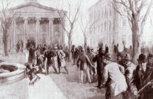 A man crumpled in a heap near a fountain in front of a building with columns. Four other men tend to the wounded man while scores of others mill about with rifles
