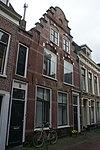 foto van Pand met trapgevel, gepleisterd en met quasi steen beschilderd, natuurstenen blokken boven vensters