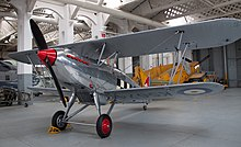 a colour photograph of a biplane in UK markings in a museum