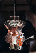 A technician stands next to one of the twin Helios spacecraft
