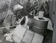 Pictured are home-made explosives packed in oil drums after having been dragged out of a culvert under a road. A soldier in a bomb suit kneels next to them.