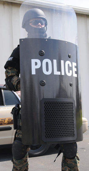 Acoustic harassment device - Law enforcement office holding a Hypershield, an acoustic hailing device used for crowd and riot control