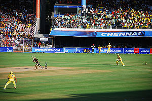 Cricketers in a game in front of nearly-full stands.