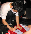 Ichirou Agata signs a Rising Sun Flag for a fan.png