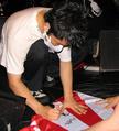 Ichirou Agata signs a Rising Sun Flag for a fan.png