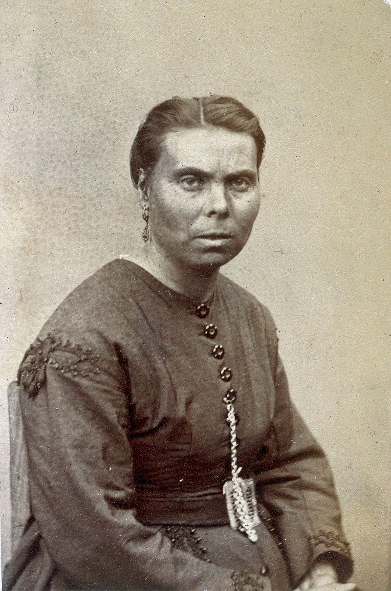 Portrait en photographie sépia d'une femme en robe simple, portant quelques festons. La femme, qui porte des boucles d'oreilles, fixe l'objectif d'un regard plutôt méfiant.