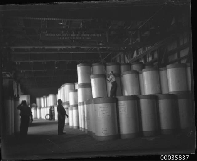 Interior view of warehouse showing workmen positioning newsprint rolls