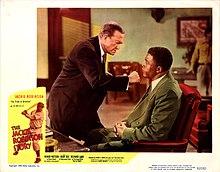 """Ein stehender Weißer schüttelt die Faust unter dem Kinn eines sitzenden Schwarzen, der ruhig reagiert.  Das eingefügte Bild eines schwarzen Baseballspielers am Schläger ist mit der Überschrift """"The Jackie Robinson Story"""" überlagert."""