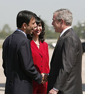 President George W. Bush (right) is greeted by...