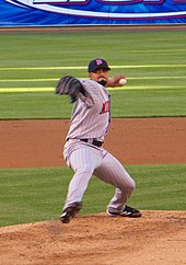 A man throwing a pitch with his left hand and one foot lifted off the ground