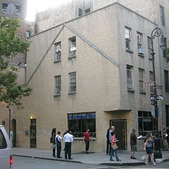 "A gray stucco-faced building seen from across a street, with a brown and white sign saying ""W. 10th ST"" and people on the sidewalk in front."