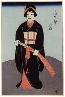 Colour print of a man in fancy dress an makeup holding a sheathed sword