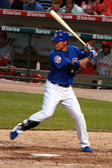 "A man in a blue batting helmet with a ""C"" on it, blue baseball jersey, white pinstriped pants, and a shin-guard on his right shin stands at home plate holding a baseball bat in a left-handed batting stance with his right foot lifted off of the ground."