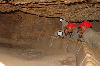 Tracking in Caves - Ui Kxunta and Thui Thao inspect the tracks in Niaux Cave