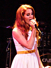Lana Del Rey is holding a mic in her hand and performing live
