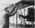 Lt. E. G. Ellyson, first naval aviator, starting engine. - NARA - 295603.tif