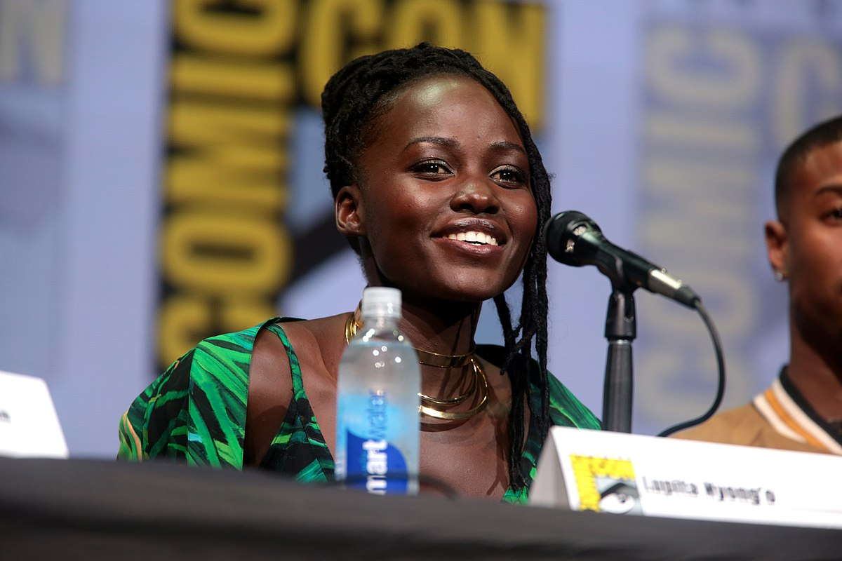 """Source: Wikimedia Commons. Description: Lupita Nyong'o smiles while sitting behind a mic during a """"Black Panther"""" panel at San Diego Comic Con."""