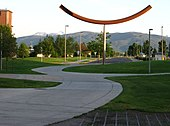 A metal sculpture on a college campus, with mountains in the far distance.