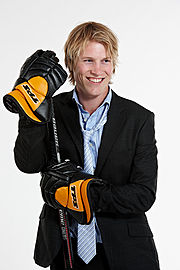 An ice hockey player standing directly in front of the camera while leaning on an ice hockey stick. He is wearing a black suit with a blue shirt and tie and is wearing black and orange hockey gloves.