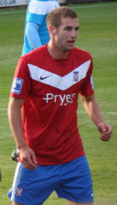 A man with brown hair who is wearing a red top and blue shorts. He is standing on a grass field.