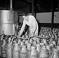 Melkfabriek man vult de melkbussen, Bestanddeelnr 252-9446.jpg