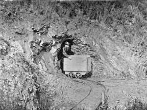 English: Gold miner with cart emerging from a ...