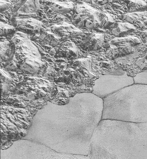 Solid nitrogen on the plains of Sputnik Planitia on Pluto next to water ice mountains Mountainous Shoreline of Sputnik Planum (PIA20198).png