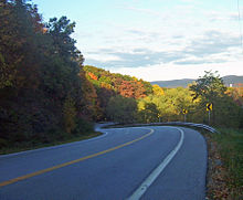 A curving highway descending into the left of the image surrounded by woods, some of which are showing fall color. Mountains loom in the distance on the right.