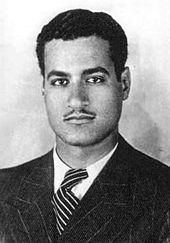 En mann iført en tweed, pinstriped jakke og et slips.  Håret er hevet og svart, og han har en tynn bart.
