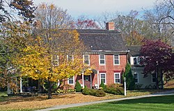 A brick house with rounded black roof and two chimneys behind two trees, one of which has lost half of its yellowed leaves which blanket the ground below, the other of which is dark red. The house has a wooden wing on the right and a less visible covered porch on the left