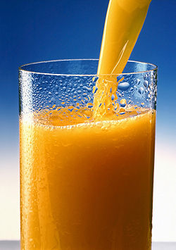Orange juice being poured into a nearly-full condensation-covered glass