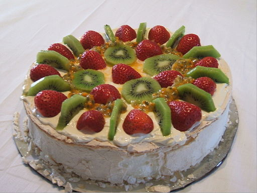 Pavlova dessert with topping of kiwifruit, strawberries and passionfruit.