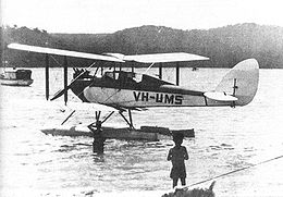 Single-engined biplane on floats, parked on the water with two boys in foreground