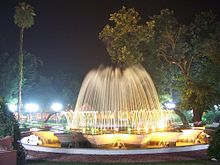 Ornate fountain at night, surrounded by trees