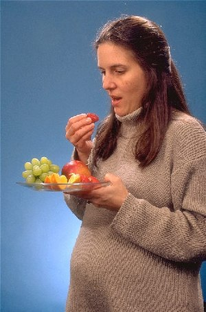 Nutrition and pregnancy - Pregnant woman eating fruit.