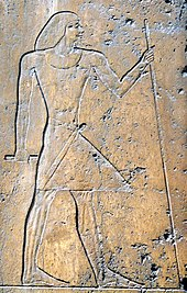 Relief on stone showing the profile of a man wearing a linen robe and holding a staff.