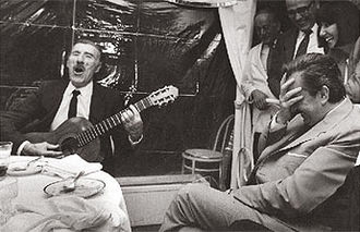 Edmundo Rivero - Rivero singing with his guitar while then president of Argentina, Raúl Alfonsín (sitting in front of him) and other people laugh (1984).