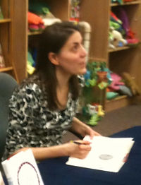 Stead, a black haired woman in her 40s, sits at a table and signs a book while looking slightly upward. Behind her are wooden shelves filled with colorful toys.