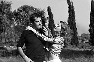 A man (Roger Vadim) standing with a dog on his shoulder with a woman (Jane Fonda) next to him.
