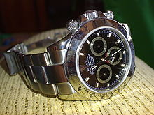 A wristwatch manufactured by the Swiss brand Rolex. The watch is constructed from stainless steel with a sapphire crystal covering a black dial. The watch has a timing feature which uses the large seconds hand which makes one complete revolution over a single minute, and includes three sub-dials. Two of these sub-dials track elapsed minutes and hours, and the other sub-dial tracks seconds for the current time, as the main seconds hand is used for the timing feature.
