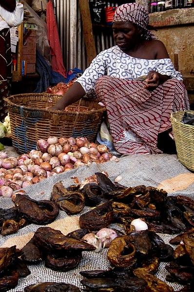 Anziana vende pesce essiccato e cipolle ad un mercato locale, Burkina Faso
