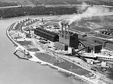 A factory with three smoking chimneys on a river bend, viewed from above