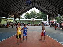 De jeunes joueurs de basket-ball sur un terrain aux Philippines.