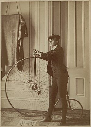 Frances Benjamin Johnston - Self-portrait by Johnston, dressed as a man, sporting a fake mustache and holding a bicycle, ca. 1890.