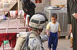 Sgt. Tyson R. Rolland gives a piece of candy to a young boy DVIDS10471.jpg