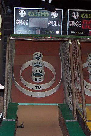 "Skee-Ball - More traditional skee ball machines like this one do not include the two additional ""100 points"" holes, located on the uppermost corners of the machine, on either side of the ""50 points"" hole."