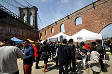 People crowd around white tents in the foreground next to a red brick wall with arched windows. Above and to the left is a towering stone bridge.