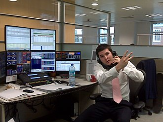 Stock - A stockbroker using multiple screens to stay up to date on trading