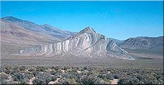 Geology of the Death Valley area - Striped Butte in Butte Valley. Steeply tilted limestone beds of the Permian Anvil Spring Formation. A major fault behind the butte separates it from Precambrian Noonday and Johnnie Formation rocks, about ½ billion years older. (USGS photo)